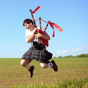 Happy Scottish man in kilt playing bagpipes
